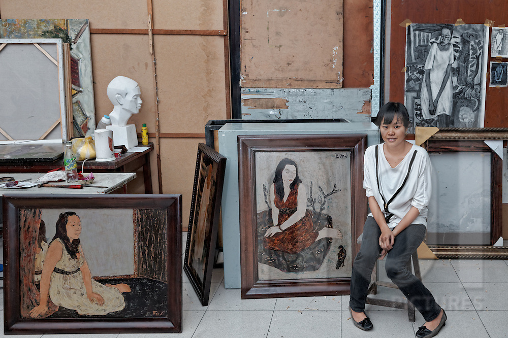 HCMC Fine Arts student sits in a studio surrounded by art pieces created by traditional mediums such as silk and lacquer painting, Ho Chi Minh City, Vietnam, Southeast Asia