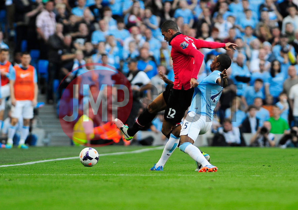 Manchester United's Chris Smalling and Manchester City's Fernandinho jostle for the ball - Photo mandatory by-line: Dougie Allward/JMP - Tel: Mobile: 07966 386802 22/09/2013 - SPORT - FOOTBALL - City of Manchester Stadium - Manchester - Manchester City V Manchester United - Barclays Premier League