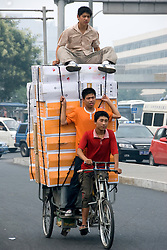Men transporting computers on tricycle in Zhongguancun High Technology district of Beijing