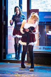 "© Licensed to London News Pictures . 24/12/2016 . Manchester , UK . Two women dressed as Santa Claus leave a takeaway on Deansgate . Revellers out in Manchester City Centre overnight during 2016's second "" Mad Friday "" , named for historically being one of the busiest nights of the year for the emergency services in the UK . Photo credit : Joel Goodman/LNP"