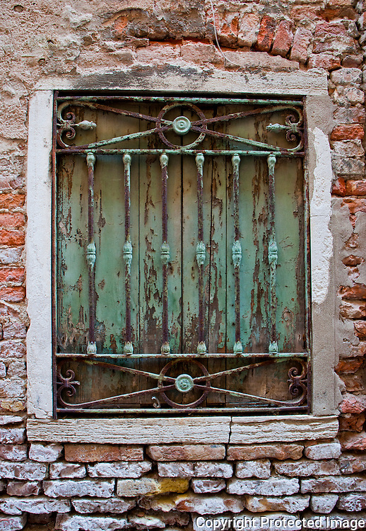 Close-up of a weathered, boarded up, metal grated window in a crumbling brick wall in Venice, Italy.