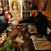 Mitch McCamey, owner of KOK, points out the different types of food he and his staff set out for the children from Tupelo's Children's Mansion for dinner on Monday night. Up to 60 children were fed and provided gift baskets by Farmhouse.