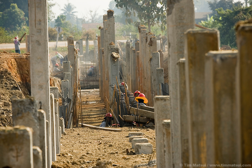 "Construction workers build the foundation for a new border crossing station in Mae Sai, northern Thailand, on the Thai/Myanmar (Burma) border on 14 January, 2007. This second, larger crossing is opening to handle an expected increase of cross-border traffic as the ""Asian Highway"" is built to facilitate transport in the Greater Mekong Sub-Region, from China to Thailand, Laos, Cambodia, Myanmar (Burma), and Vietnam. Historically plagued by human trafficking of the area's poorer hill tribe children, according to local NGO workers the border crossing in Mae Sai is likely to grow in importance as a transit point for trafficking victims as the new transportation infrastructure eases the movement of people from poorer countries like Laos and Myanmar (Burma)."