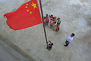 QIANNAN, CHINA - MAY 31: (CHINA OUT) <br /> <br /> Six-pupil School In Mountain Of Qiannan<br /> <br /> The only teacher Wu Guoxian and pupils hold a flag-rising ceremony at Gugang primary school in a mountain in Longli County on May 31, 2016 in Qiannan Buyei and Miao Autonomous Prefecture, Guizhou Province of China. Gugang primary school with only one teacher and six students was located in the mountain where the traffic was blocked in Qiannan. 50-year-old Wu Guoxian had been teaching in this school for 33 years and taught over 1,000 students. More and more people went out of the village to work in the cities leaving their children and the old in the mountain. Five under-school-age kids whose parents left for work also stayed at the school.<br /> ©Exclusivepix Media