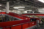 "50-70,000 pieces of British Airways baggage a day travel through these 11 miles of conveyor belts which were installed in a 5-storey underground hall beneath the 400m (a quarter of a mile) length of Terminal 5 at Heathrow Airport. T5 alone has the capacity to serve around 30 million passengers a year and was completed in 2008 at a cost of £4.3bn. The system was designed by an integrated team from the airport operator BAA, BA and Vanderlande Industries of the Netherlands, and handles both intra-terminal and inter-terminal luggage. There are four colour codes: Yellow for out-of-gauge (oversized, like golf clubs); dark blue for not x-rayed; light blue for transfer and red, meaning the item has been subjected to 12 seconds of x-ray scanning. From writer Alain de Botton's book project ""A Week at the Airport: A Heathrow Diary"" (2009)."