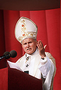 Pope John Paul II during his historic visit to Paris in 1980 addresses pilgrims in a speech from a podium while wearing his papal mitre and robes