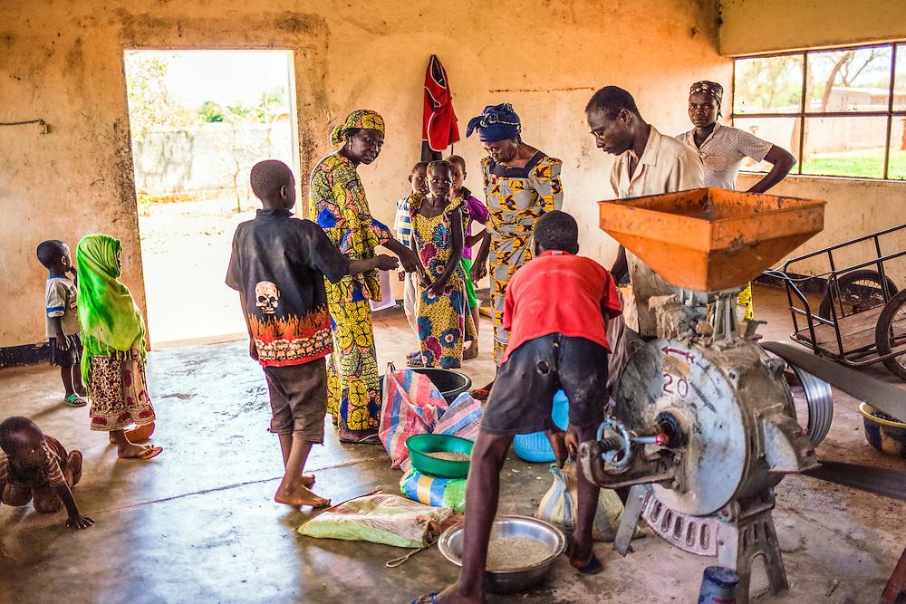LÉGENDE: Les femmes apportent leurs noix de Karité pour faire moudre. Albertine vient voir le déroulement des activités. LIEU: Centre COFEMAK, Koumra, Tchad. PERSONNE(S): Albertine Toulhade (au milieu) avec les clients.