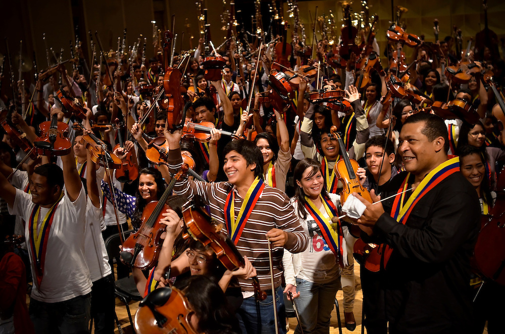 "Children trained by El Sistema do a ""wave"" with their instruments after performing for Gustavo Dudamel, Antonio Abreu, and members of the Los Angeles Philharmonic in Caracas on Februrary 16, 2012.  Some critics believe that Antonio Abreu and Gustavo Dudamel, leaders of El Sistema, Venezuela's internationally acclaimed, state-funded classical music education program that serves underpriviledged children, should take a political stand against Chavez and his anti-democratic tendencies."