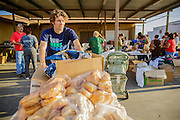07 AUGUST 2012 - TOLLESON, AZ:   NEIL MCDONAGH, a volunteer at the food bank in Tolleson, AZ, brings a cart of food out to a waiting truck Tuesday. The Tolleson food bank has been operating for more than 20 years. It used to serve mostly the families of migrant farm workers that worked the fields around Tolleson but in the early 2000's many of the farms were sold to real estate developers. Now the food bank serves both farm worker families and people who lost their homes in the real estate crash, that his Phoenix suburbs especially hard. More than 150 families a day are helped by the Tolleson food bank, an increase of more than 50% in the last five years.  PHOTO BY JACK KURTZ