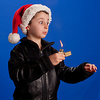 Young boy with santa elf hat, leather coat and zippo lighter looking surprised, on a blue background.