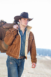cowboy with a saddle over his shoulder walking on a ranch