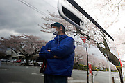"Kazuyuki Takita, 32, stands by his truck after taking photos of the cherry blossom along a street famed for having one of Japan's longest cherry blossom ""tunnels"" in Tomioka, Fukushima Prefecture, Japan on Wednesday 20 April  2011. Takita, who hails from Iwaki about one-hour's drive away, was visiting the town  to see the famed cherry trees despite the trees being located just a few miles from the leaking Fukushima No. 1 nuclear power plant..Photographer: Robert Gilhooly"
