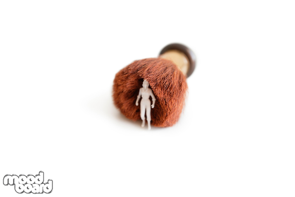 Figurine with a shaving brush over white background