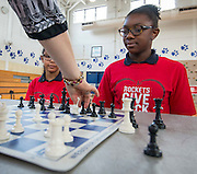 Arial Baker, left, and Kailee Bradford watch chess grandmaster Susan Polgar make a move during their game at Ryan Middle School, September 15, 2014.