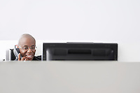 Office worker sitting in office cubicle using telephone smiling