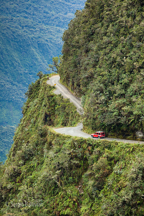 A 4x4 vehicle negotiates the convoluted Yungas mountain range near La Paz, Bolivia. as seen from up high on a narrow mountain road that winds it way into the   lower tropical lowlands.