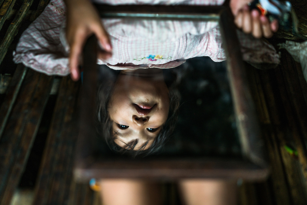 MYITKYINA, MYANMAR - MARCH 13th, 2016: A young girl plays with a mirror in her home in Shwezet IDP village. Nearly 500 people were forced to relocate here in 2011 because of escalated fighting in their home villages between the Kachin Independence Army, KIA, and the Burmese government.