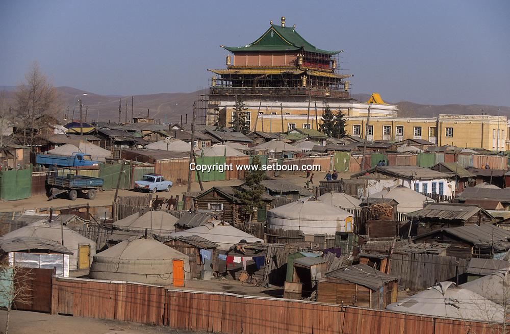 Mongolia. Ulaanbaatar. yurts area around Gandan monastery OulanBator    / Quartier de yourtes à OULAN BATOR. / La capitale s'élève dans une vallée du massif du KENTI. Un couple regagne leur domicile en banlieue, dans un des quartiers de yourtes délimités par de hautes palissades en bois. Au second plan se dresse le centre ville avec ses bâtiments administratifs et immeubles d'habitation en béton. (Partie Nord-Ouest de OULAN BATOR,  / 4    L921009c  /  P0002740