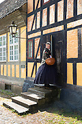 Costume character and half-timbered building at Den Gamle By, The Old Town, open-air folk museum at Aarhus,  East Jutland, Denmark