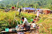 Kachin refugee housewives ai Je Yang Hka near China Myanmar boarder Lai Za. Refugee school teachers washing clothes during free time at noon.