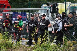 Denham, UK. 24 July, 2020. Members of the emergency services, enforcement agents and HS2 staff observe environmental activists from HS2 Rebellion who had been trying to prevent the destruction of an ancient alder tree in connection with works for the HS2 high-speed rail link in Denham Country Park. A large policing operation involving scores of officers from the Metropolitan Police, Thames Valley Police, City of London Police and Hampshire Police as well as the National Eviction Team was put in place to enable HS2 to remove the tree.