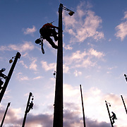 Apprentice linemen practice pole climbing in the early morning at a training center in southern Indiana.