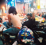 A couple sitting on a motorbike, New York, USA