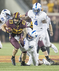 August 31, 2017 - Minneapolis, MN, USA - Minnesota running back Shannon Brooks (23) runs for a first down despite defensive pressure from Buffalo defensive end Charles Harris during the fourth quarter at TCF Bank Stadium in Minneapolis on Thursday, Aug. 31, 2017. The host Golden Gophers won, 17-7. (Credit Image: © Elizabeth Flores/TNS via ZUMA Wire)