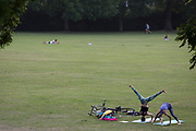 During the UK's Coronavirus lockdown, the May Bank Holiday brought warm temperatures for Londoners who stayed late to exercise, young women practice yoga in Ruskin Park, in Lambeth, on 24th May 2020, in London, England.