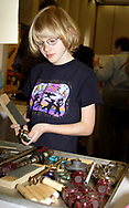 In the Engineers Club booth, Kaitlin Wieder, 9, from Wright Patterson AFB was given a problem to solve, and looks through various items in trays to determine which will be the best to use to solve it.