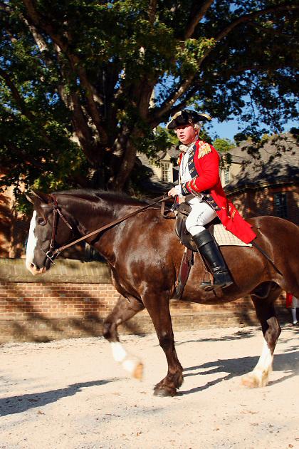 male Revolutionary War interpreter British General Benedict Arnold on horseback talking; dress uniform; redcoat; Colonial Williamsburg; Virginia; VA; summer