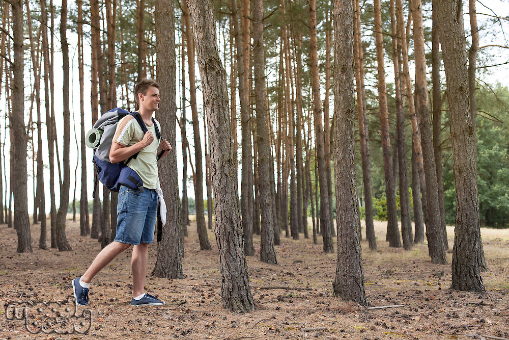 Full length of young man with backpack walking in forest