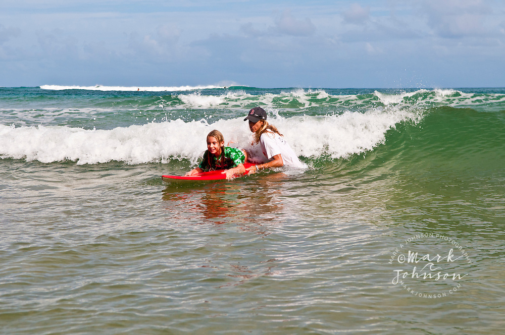 Mother teaching her 7 year old girl surfing at Hanalei Bay, Kauai, Hawaii