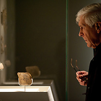 A visitor looks at sculptures during the press preview of the 'Ice Age Art - Arrival of the modern mind' exhibition at The British Museum in London. The exhibition, curated by Jill Cook, opens in London on the 7th of February and presents masterpieces of Ice Age sculpture, ceramics, drawing and personal ornaments, created over 20,000 years ago.