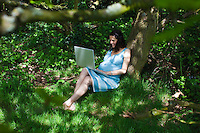 Pregnant woman using laptop in woods