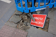 A Closed Footpath sign fallen into a hole during pavement works in the south London borough of Lewisham.