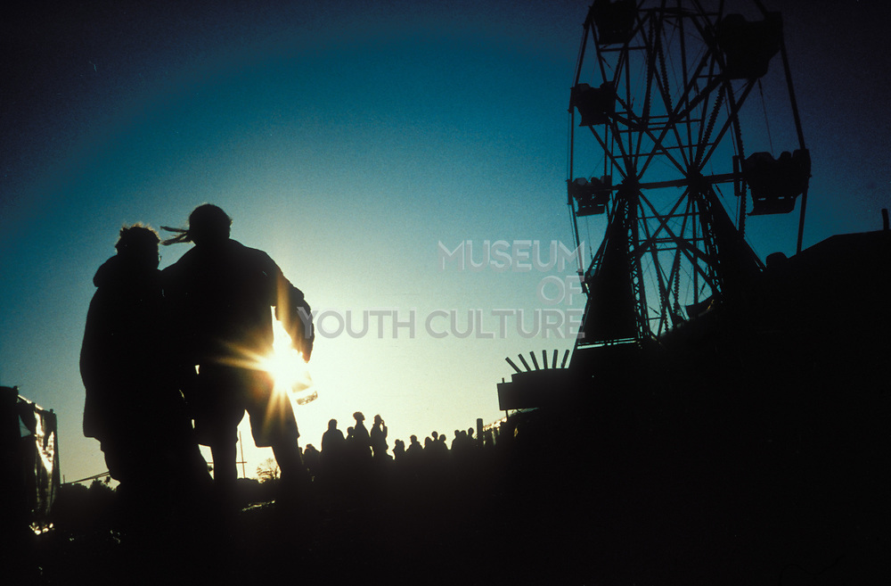 Silhouettes of people and a ferris wheel at the Glastonbury Festival, UK 1995