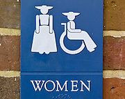 A blue and white women's ADA restroom sign shows colonial garb and wheelchair at Colonial Williamsburg, the historic district of Williamsburg, Virginia.