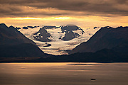 A storm clouds part at sunset over Grewingk Glacier in the Kachemak Bay State Park from Homer, Alaska.