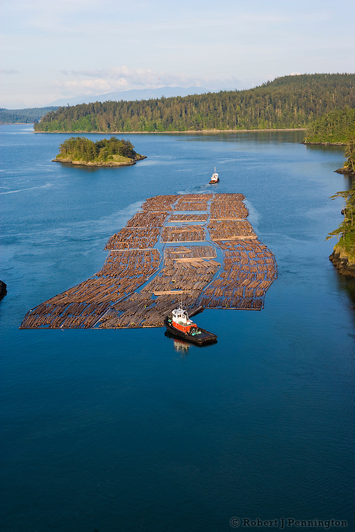 Two tugboats navigate a timber raft through narrow passages and islands in the Pacific Northwest Puget Sound.