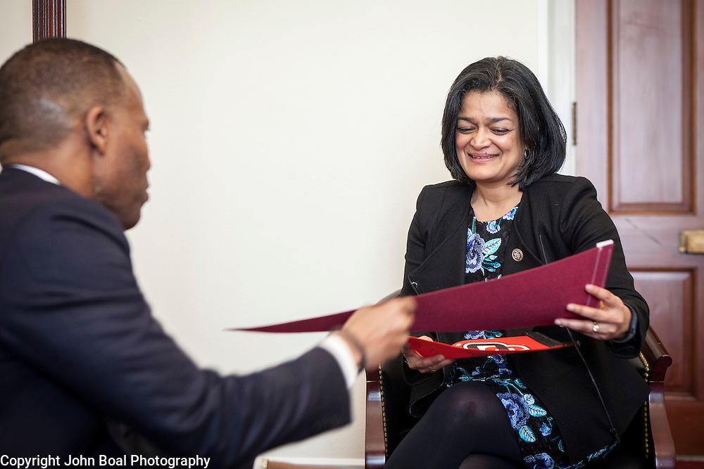 Representative Pramila Jayapal (D-WA, 7) receives a pennant of Seattle University from Isiaah Crawford of the National Association of Independent Colleges and Universities, on Tuesday, January 31, 2017.  This was the last of four 30-minute meetings with constituent advocacy groups during the day.  John Boal photo/for The Stranger