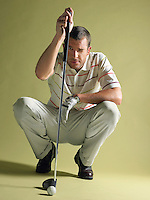 Golfer squatting holding golf club and squinting