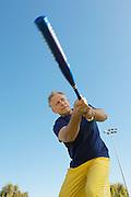 Senior man swinging baseball bat