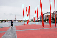 Grand Canal Square with red angled light sticks in Dublin's docklands Ireland, man walking by with umbrella, talking on mobile phone.