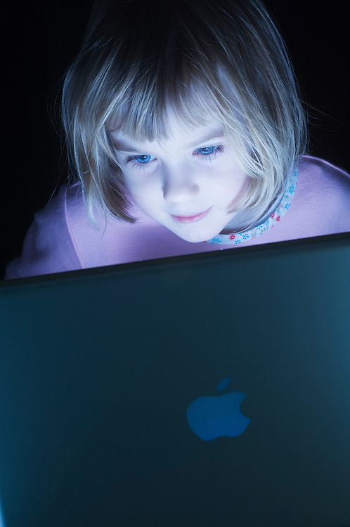 Girl, 4, engrossed by a computer