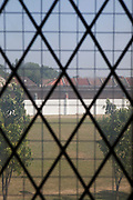 Looking out of a cell window across the prison grounds to the perimeter wall, topped with razor wire. HMP Kingston, Portsmouth, United Kingdom. Kingston prison is a category C prison holding indeterminate sentenced prisoners.