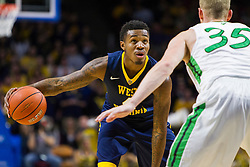 Dec 17, 2015; Charleston, WV, USA; West Virginia Mountaineers guard Daxter Miles Jr. (4) looks to make a move around Marshall Thundering Herd guard Austin Loop (35) during the first half at the Charleston Civic Center . Mandatory Credit: Ben Queen-USA TODAY Sports