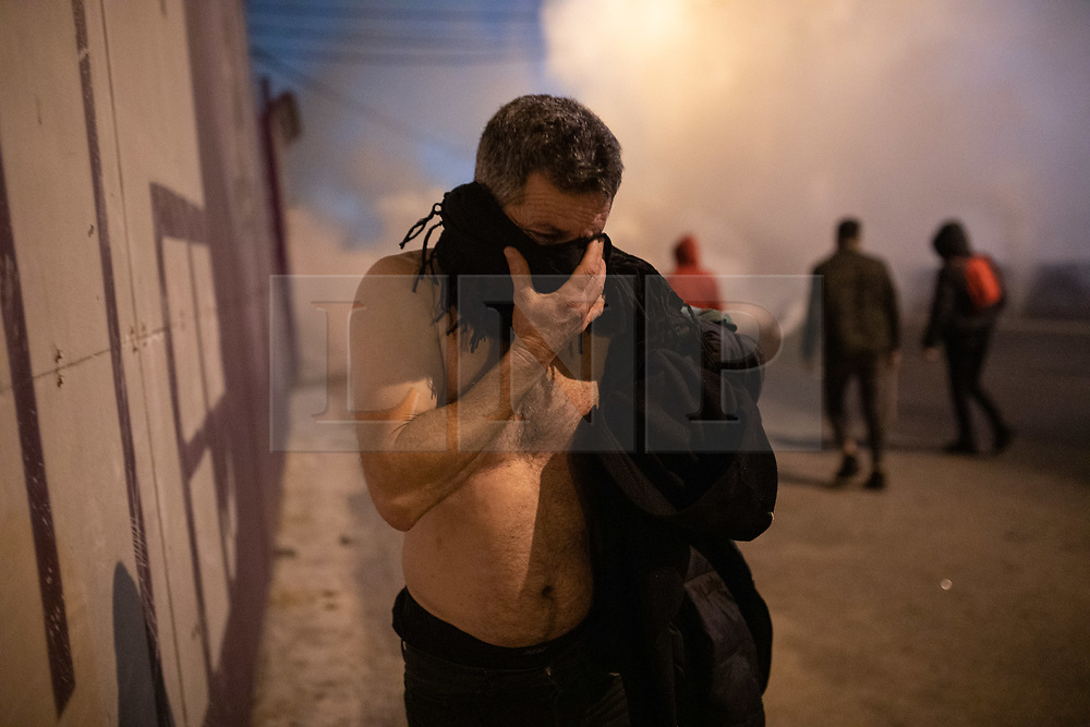 """© Licensed to London News Pictures. 22/01/2020. Beirut, Lebanon. A topless man walks away from tear gas as demonstrators riot on a main highway in Beirut following the announcement late last night that a government has been formed. Police respond with tear gas and water cannon against the anti-government demonstrators. Violence has been escalating in the capital following a """"week of wrath"""", where demonstrators were campaigning against government corruption and economic crisis. Photo credit : Tom Nicholson/LNP"""