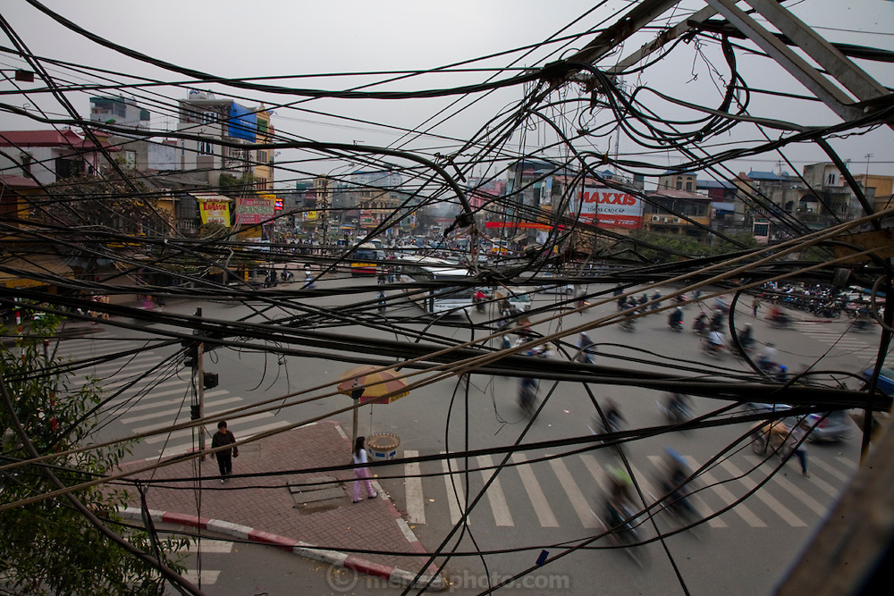 Tangled electricity cables hang over a busy street in Hanoi. Vietnam's transport and communication infrastructure is weak but the economy is expanding rapidly.