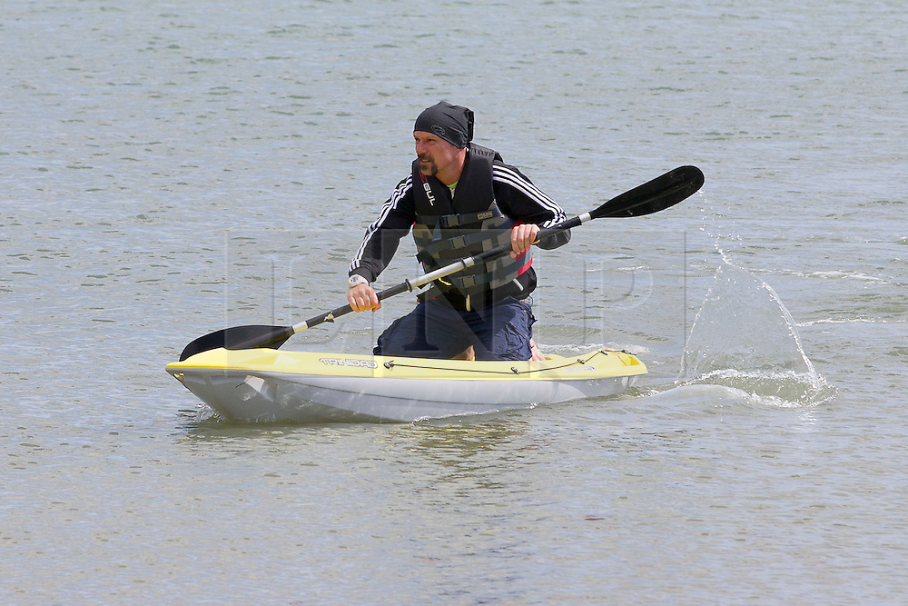 © London News Pictures. United Kingdom, Swanage : A man paddles a canoe on the sea on a a sunny day in Swanage, Dorset, on June 3, 2015. Photo credit: LNP